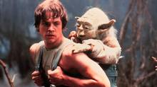 Mark Hamill as Luke Skywalker carrying Yoda, in The Empire Strikes Back.