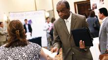 Faidy Jacques, 53, hands his resume to a job recruiter at a job fair in Melville, New York (REUTERS/Shannon Stapleton)
