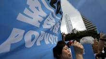 """Pro-democracy supporters raise banners that read """"eferendum"""" during a kickoff ceremony for a referendum on democracy in Hong Kong on June 20, 2014. (VINCENT YU/ASSOCIATED PRESS)"""