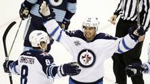 Winnipeg Jets Tim Stapleton (14) congratulates teammate Alexander Burmistrov (8) on his goal against the Pittsburgh Penguins in the first period of their NHL hockey game in Pittsburgh, Pennsylvania February 11, 2012. (JASON COHN/Reuters)