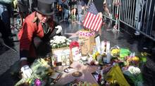 Gregg Donovan places flowers on the star of actor-comedian Robin Williams at a makeshift memorial along the Hollywood Walk of Fame in Los Angeles on Aug. 12, 2014. (Nick Ut/Associated Press)