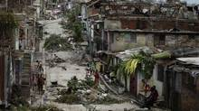 People walk on a street littered with debris after Hurricane Sandy hit Santiago de Cuba Oct. 26, 2012. Cuba's coffee crop was decimated by the killer storm, with 20 to 30 per cent of the crop on the ground, processing centres damaged, and renovated plantations wrecked. (DESMOND BOYLAN/REUTERS)