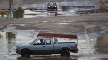 A truck with a boat atop of it moves through the flooded city of Calgary June 22, 2013. (John Lehmann/The Globe and Mail)