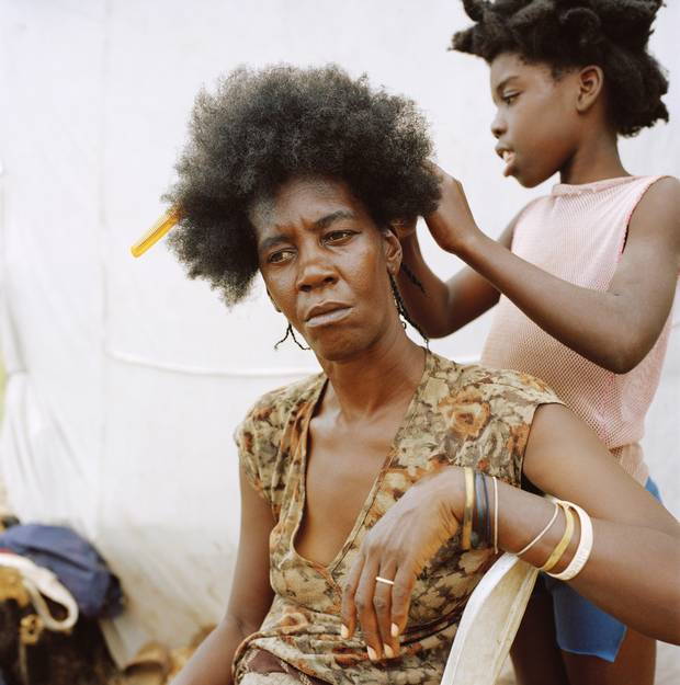 Anse-à-Pitres, Haiti — Emani Escaliste has her hair done by one of her daughters at a displacement camp where she now lives with her children after she was threatened and her house was burnt down in the Dominican Republic.