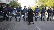 An elderly woman walks in front of riot policemen guarding the Orthodox cathedral of Saint Dimitrios in Thessaloniki, northern Greece, during celebrations Friday, Oct. 26, 2012, marking 100 years since the city's liberation from the Ottoman empire. Police secured the area around the cathedral to prevent anti-austerity protests that cancelled last year's military parade. (Nikolas Giakoumidis/AP)