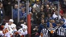 Referees get in the way of Vancouver Canucks head coach John Tortorella as he screams at the Calgary Flames bench during an NHL hockey game. (JONATHAN HAYWARD/THE CANADIAN PRESS)