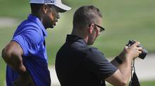 Tiger Woods, left, looks at a camera screen with coach Sean Foley on the driving range (Phil Long/The Associated Press)