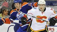 Edmonton Oilers' Colin Fraser, left, against the Calgary Flames Cory Sarich during second period NHL hockey action in Edmonton on Saturday, Jan. 1, 2011. THE CANADIAN PRESS/John Ulan (John Ulan)