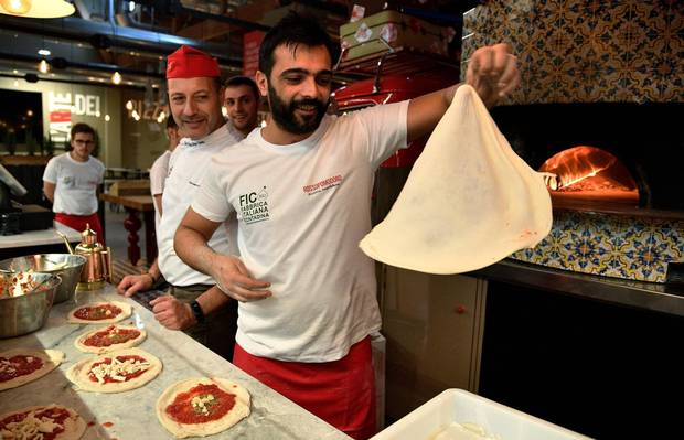 Pizza bakers prepare traditional pizza margherita r at in FICO Eataly World agri-food park in Bologna in November, 2017.