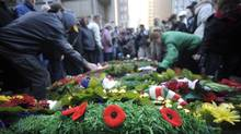 People place their poppies on the wreaths after Remembrance Day ceremonies at Old City Hall in Toronto on Nov 11 2010. (Fred Lum/Fred Lum/The Globe and Mail)