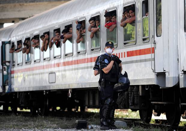 Croatian Police stand beside a train carrying migrants and refugees in a marshalling yard near Zagreb on September 18, 2015. A special train transporting some 1,500 people from Tovarnik, near the Serbian border, arrived in the Croatian capital where some Croats, recalling their own plight during the Balkan wars in the 1990s, offered aid.