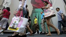 In this July 5, 2011 file photo, pedestrians carrying shopping bags make their way along Fifth Avenue in New York. (Seth Wenig/Seth Wenig/The Associated Press)
