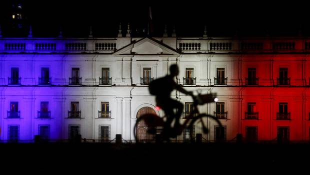 La Moneda government house is illuminated with the blue, white and red colours of the French flag in Santiago on Nov. 15, 2015.