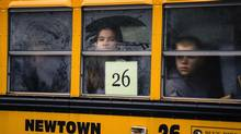 Children look out through condensation on the windows of a school bus numbered 26 as it pulls into Newtown High School in Newtown, Connecticut December 18, 2012. The schools of Newtown, which stood empty in the wake of a shooting rampage that took 26 of their own, will again ring with the sounds of students and teachers on Tuesday as the bucolic Connecticut town struggles to return to normal. (LUCAS JACKSON/REUTERS)