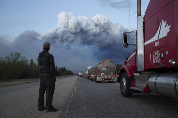 Drivers of a resupply convoy stand outside their vehicles south of Fort McMurray as a wildfire blocked the only highway to the city. Nearly 25,000 of Fort McMurray's 90,000 or so residents fled north to isolated oil industry work camps when the city was ordered evacuated, but supplies there quickly ran low.
