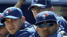 Toronto Blue Jays starting pitchers Dustin McGowan (L), Brett Cecil (C) and Ricky Romero (R) watch from the dugout before their MLB Grapefruit League baseball game against the Boston Red Sox in Dunedin Florida, March 7, 2012. REUTERS/Mike Cassese (Mike Cassese/Reuters)