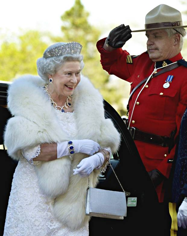 A Mountie salutes as the Queen arrives at an official dinner in Edmonton on May 24, 2005.