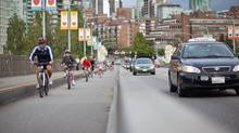 "Cyclists make their way over the Burrard Bridge bike lane in Vancouver. Local cycling advocacy groups are calling on B.C.'s provincial parties, heading into the May 14 election, to invest $75-million a year toward a ""comprehensive cycling strategy."" (Brett Beadle for The Globe and Mail)"