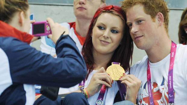 Britain's Prince Harry poses for photgraphs with Great Britain swimming gold medalist Jessica-Jane Applegate at the Aquatics Centre during the London 2012 Paralympic Games September 4 2012. (POOL/REUTERS)