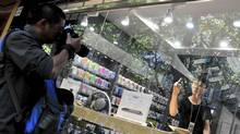 An employee in a fake Apple Store gestures with his middle finger to a photographer trying to take pictures of the store in Kunming, Yunnan province July 21, 2011. (CHINA DAILY/REUTERS)