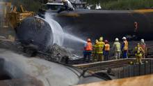 Crews work in the area of the derailed tanker cars in Lac-Mégantic, Que., on July 14, 2013, after a train derailment and subsequent fires and explosions destroyed much of the downtown area of the picturesque Quebec town. (PETER POWER/THE GLOBE AND MAIL)