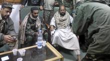 A mobile phone picture taken by one of his guards shows Saif al-Islam Gaddafi sitting with his captors in Obari airport Nov. 19, 2011. (Reuters/Reuters)