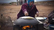 A Syrian woman who fled from the violence in her village, bakes bread at a camp, in the village of Atmeh, near the Turkish border with Syria, Nov. 8, 2012. (Khalil Hamra/AP)