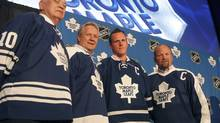 Toronto Maple Leafs new captain Dion Phaneuf, second from right, is flanked by former captains George Armstrong, Darryl Sittler and Wendel Clark, each wearing a jersey reflective of their era, during a news conference in Toronto. (MIKE CASSESE/Reuters)