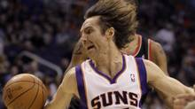 Phoenix Suns guard Steve Nash, front, loses control of the ball as he attempts to spin around Portland Trail Blazers center Marcus Camby, rear, on his way to the basket in the first quarter of an NBA basketball game Friday, Jan. 14, 2011, in Phoenix. (Paul Connors/UPI)