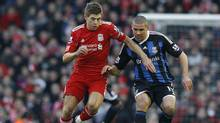 Liverpool's Steven Gerrard (L) challenges Stoke City's Jonathan Walters (R) during their English Premier League soccer match at Anfield in Liverpool, northern England, January 14, 2012. (PHIL NOBLE/REUTERS)