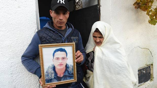 Walid Amri (L), the brother of 24-year-old Anis Amri, the prime suspect in Berlin's deadly truck attack, poses with a portrait of his brother in front of the family house in the town of Oueslatia, in Tunisia's region of Kairouan on December 23, 2016.