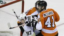 ttsburgh Penguins' Sidney Crosby (87) gets squeezed between Philadelphia Flyers goalie Ilya Bryzgalov and defenceman Andrej Meszaros during the third period of an NHL hockey game Saturday, Jan.19, 2013, in Philadelphia. (Associated Press)