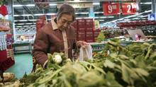 A customer looks at vegetables at a shop in Shanghai on Tuesday. China appears on track to avoid an abrupt economic slowdown with possible global repurcussions after growth eased to its lowest level in 2 1/2 years in the last quarter of 2011. (STR/Associated Press)