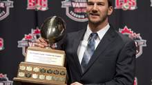 McMaster University quarterback Kyle Quinlan poses with the Hec Crighton trophy during the CFL awards in Toronto Thursday, November 22, 2012. (Sean Kilpatrick/THE CANADIAN PRESS)