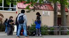 Parents and students gather at False Creek Elementary School after a human hand was delivered to the school earlier in the day in Vancouver, B.C., on Tuesday June 5, 2012. A human foot was also delivered to another Vancouver school Tuesday (Darryl Dyck/The Canadian Press)