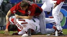 Canada's Jay Johnson, top left, and Mexico's Eduardo Arredondo fight during the ninth inning of a World Baseball Classic game, Saturday, March 9, 2013, in Phoenix. (Associated Press)