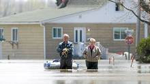 A man and woman make their way along a street immersed by flood waters from the Richilieu River in the town of Saint-Blaise-Sur-Richelieu, Que., Sunday, May 8, 2011. (Graham Hughes/Graham Hughes/The Canadian Press)