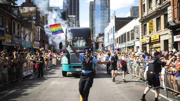 A Toronto Police Service parking-enforcement officer waves a Pride flag during the Pride Parade in 2016.