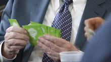 Berkshire Hathaway CEO Warren Buffett holds a hand of cards bearing a caricature of his likeness, while playing bridge with shareholders at the annual Berkshire Hathaway shareholders meeting in Omaha, Neb., in May 2009