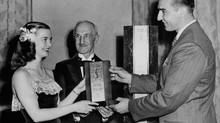 June. 1947. Barbara Ann Scott, world figure skating champion passes over a replica of the Lou March Memorial Trophy to Joe Krol, great Argonaut halfback, who was voted Canada's outstanding athlete in 1946. Smilingly observing the ceremony is Charlie Ring, Toronto sportman and member of the Marsh Trophy Selection Board. (The Globe and Mail)