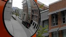 A mirror reflects a vehicle passing through the Olympic Village development in Vancouver, the social housing component of which has roused much contentious debate of late, with architect Michael Geller suggesting it might be hurting overall sales, a statement that immediately became fodder for some ugly partisan politicking. (Darryl Dyck/The Canadian Press)