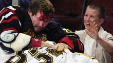 Chicago Blackhawks' Bob Probert (24) and Boston Bruins' Andrei Nazarov (62) of Russia, mix it up along the boards during a first period fight Sunday, Oct. 28, 2001 in Chicago. Both players received five minute penalties for fighting. (AP Photo/Fred Jewell) (FRED JEWELL)