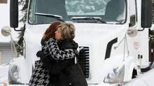 Two mourners embrace after the funeral of truck driver Christopher Fulton in London, Ont., on Saturday. (Dave Chidley/The Canadian Press)