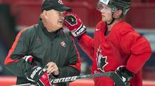 Team Canada head coach Lindy Ruff, left, chats with team captain Eric Staal during practice Thursday, May 2, 2013 at the world hockey championship in Stockholm, Sweden. (Jacques Boissinot/THE CANADIAN PRESS)