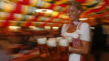 A waitress serves mugs of beer during the opening of the Oktoberfest in Berlin September 9, 2009. (FABRIZIO BENSCH)