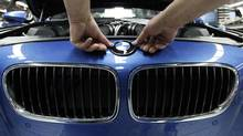 A worker puts an emblem on a BMW 5 series car at the plant in the Bavarian city of Dingolfing. (MICHAELA REHLE/Michaela Rehle/Reuters)