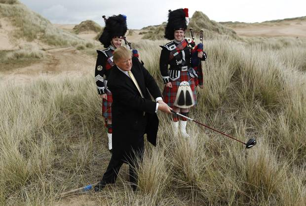 U.S. property mogul Donald Trump poses next to bagpipers during a media event on the sand dunes of the Menie estate, the site for Trump's proposed golf resort, near Aberdeen, Scotland, in 2010.