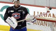 Montreal Canadiens goalie Carey Price bats down a puck during practice earlier this month prior to suffering his injury (Ryan Remiorz/THE CANADIAN PRESS)