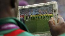 Pierre MB, a member of the Cameroon coaching staff, takes a picture of the team before their women's soccer first round Group E match against New Zealand at the City of Coventry Stadium during the London 2012 Olympic Games July 31, 2012. (ALESSANDRO GAROFALO/REUTERS)
