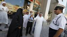 Family members and friends of 20 uprising leaders who are on trial speak to police officials outside a court in Manama September 4, 2012. (HAMAD I MOHAMMED/REUTERS)